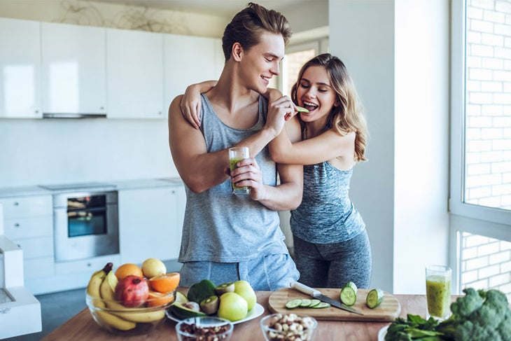 Man and woman snacking on healthy food in kitchen