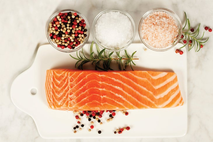 Salmon on a white board next to glass bowls of spices
