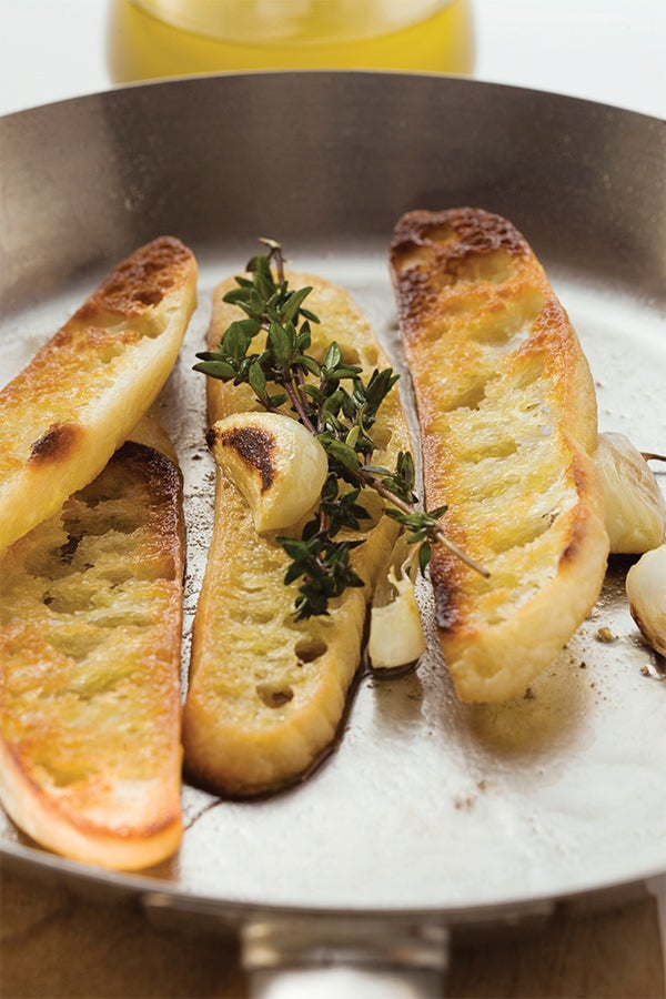 Toast slices in pan with garlic