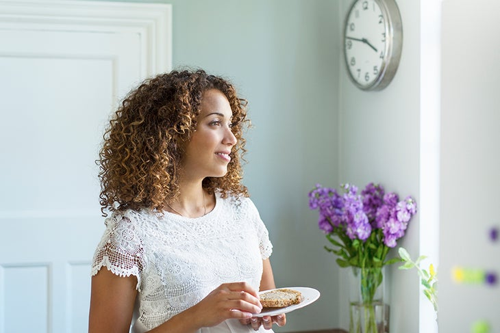 Woman eating in the kitchen near a clock