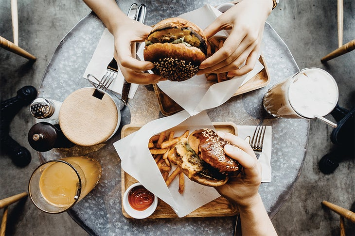 Two people eating burgers