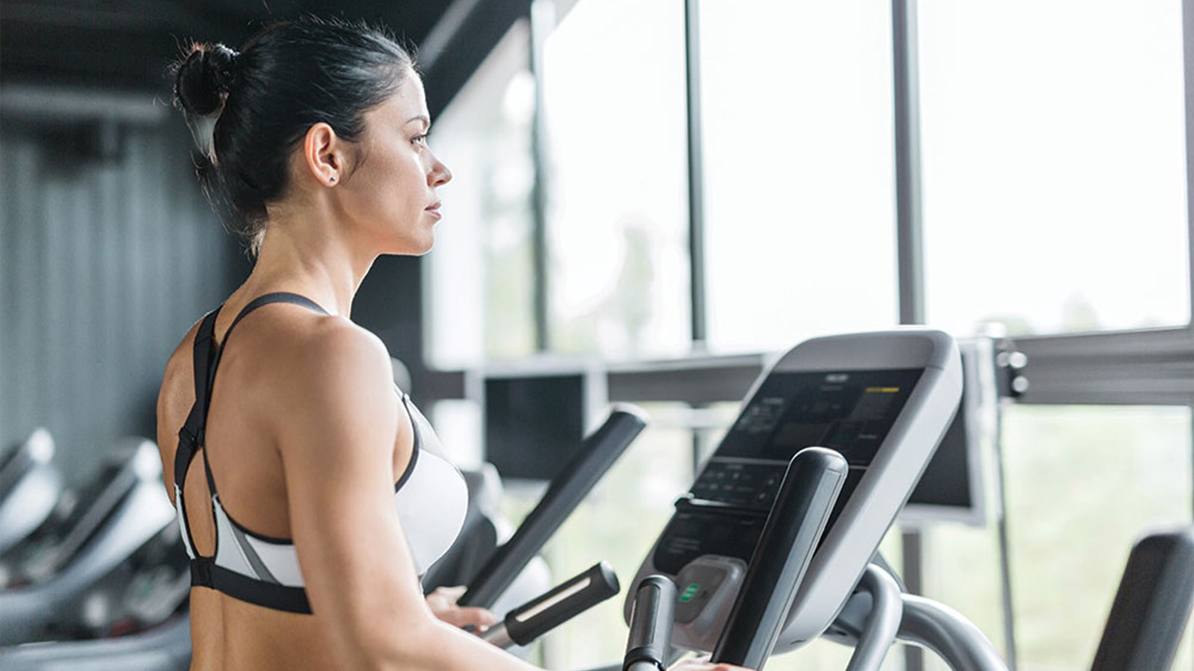 Woman in sports bra on the treadmill at the gym, looking out the window into nature.
