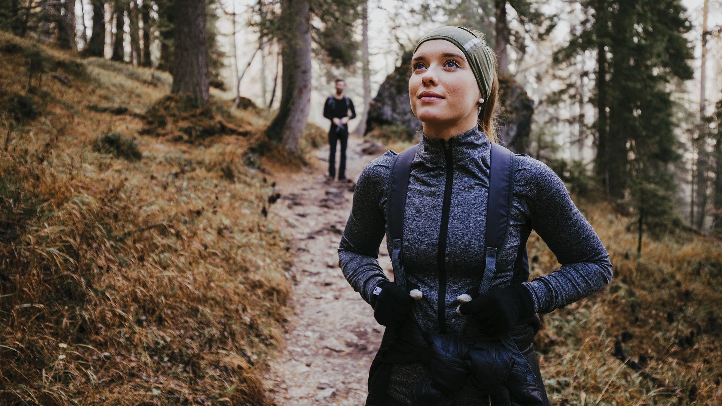 Woman and man hiking outdoors in the woods.