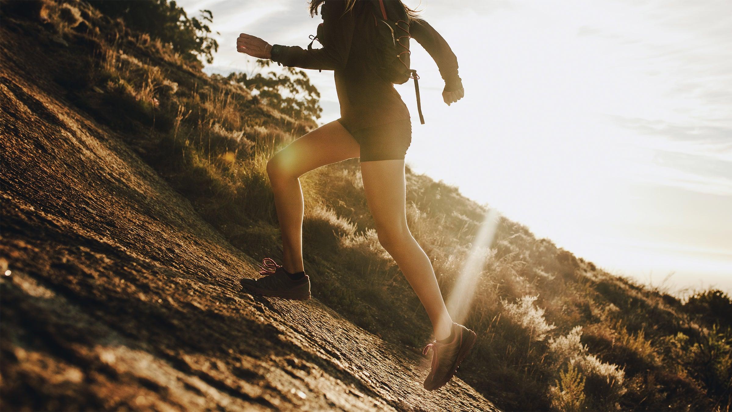 Woman running uphill outdoors.