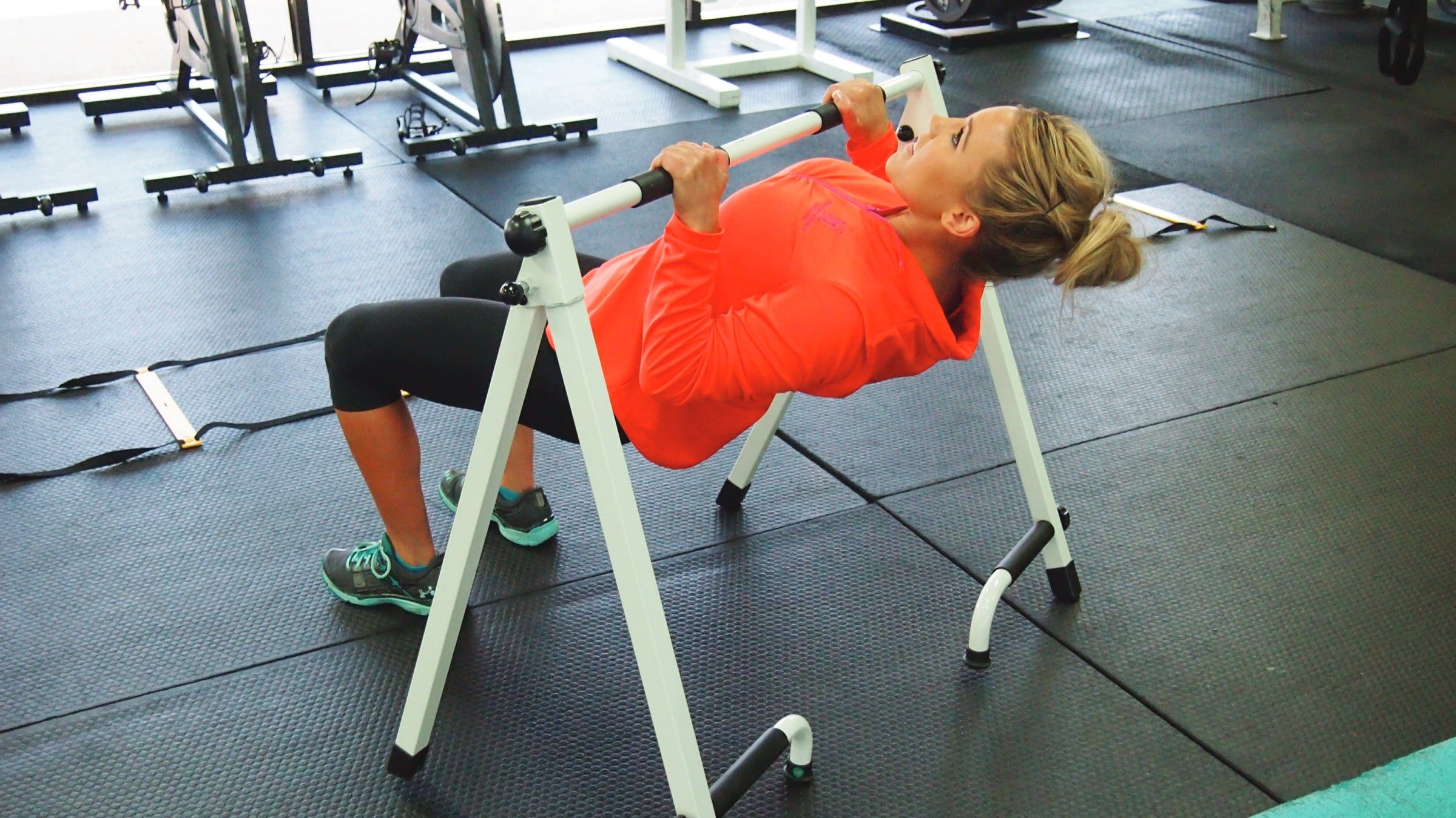 Woman using portable pull-up bar at the gym