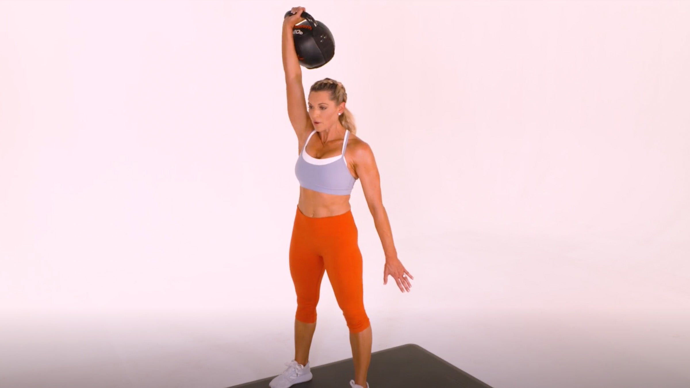 Woman demonstrating Kettlebell One-Arm Snatch