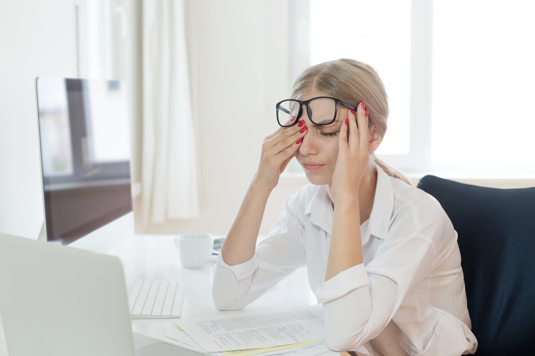 Tired woman rubbing eyes